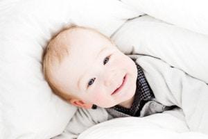 Toddler playing in a white duvet